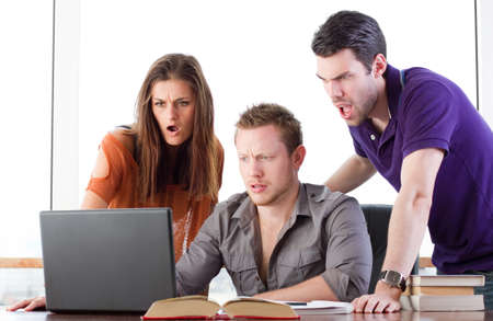reacting: Group of young people reacting to something on the computer Stock Photo