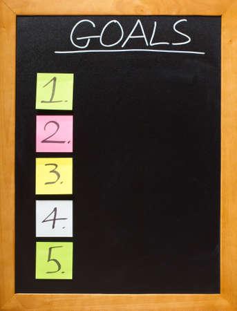 goal setting: Goals in chalk on a blamk blackboard, lots of copyspace - add your own font