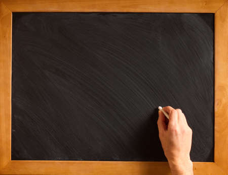 Male hand writing with chalk on a clean blackboard - add your own chalk! photo