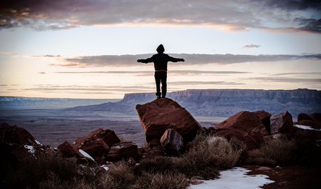 echo: Boy standing on a rock is looking stunning landscape at sunset Stock Photo