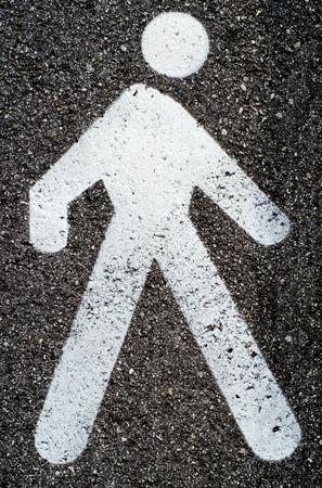 pedestrian: White pedestrian sign on asphalt