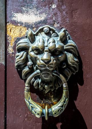 wornout: traditional Italian door knocker on worn-out wood door