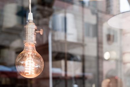 urban scene: Decorative old edison style light bulb against blurred urban scene reflecting background Stock Photo
