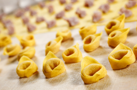 Tortellini. Italian homemade stuffed pasta made with fresh pasta kneaded with flour and eggs; stuffed with meat and parmesan cheese. Foto de archivo