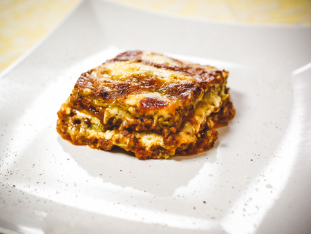 Lasagna bolognese. Typical homemade fresh green pasta cooked in oven. A portion in plate. Stock Photo