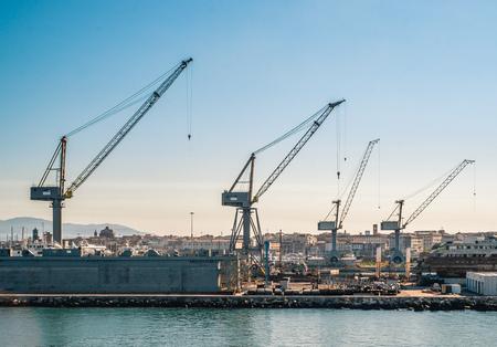 cranes and shipyards in Livorno harbor. Tuscany, Italy.