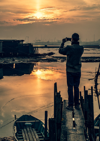 Man is taking picture with a smartphone at the sunset. Marina di Ravenna lagoon, Ravenna province, Emilia Romagna, Italy.