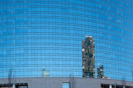 Modern buildings are reflected on the glass wall. Milan, Lombardy, Italy. Stock Photo