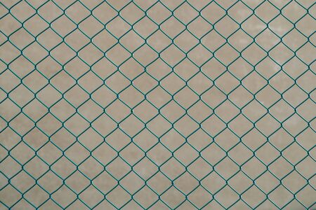Diamond shaped wire mesh coated in green plastic against a blurred wall. Background texture