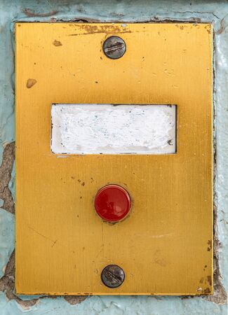 old doorbell plate with blank erased label and red button