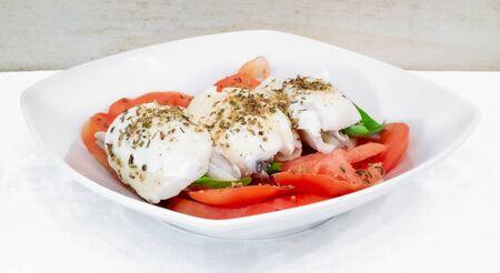Caprese salad with marinated sardines. Ingredients: tomatoes, mozzarella cheese, marinated sardines, basil and origan.
