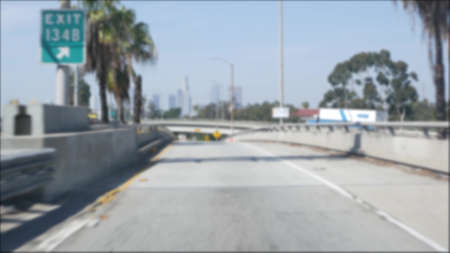 Driving on intercity freeway in Los Angeles, California USA. Defocused view from car thru glass windshield on busy interstate highway. Blurred suburb multiple lane driveway. Camera inside auto in LA.