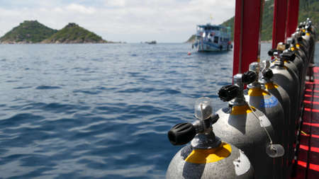 Row of oxygen tanks and diving equipment placed on modern boat in rippling ocean near Koh Tao resort, Thailand. Concept of tourist sports extreme entertainment, adventure and new experience