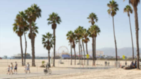 California beach aesthetic, people ride cycles on a bicycle path. Blurred, defocused background. Amusement park on pier and palms in Santa Monica american pacific ocean resort, Los Angeles CA USA.