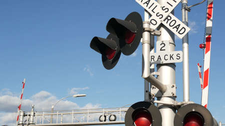 Level crossing warning signal in USA. Crossbuck notice and red traffic light on rail road intersection in California. Railway transportation safety symbol. Caution sign about hazard and train track.