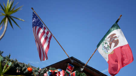 Mexican tricolor and American flag waving on wind. Two national icons of Mexico and United States against sky, San Diego, California, USA. Political symbol of border, relationship and togetherness.