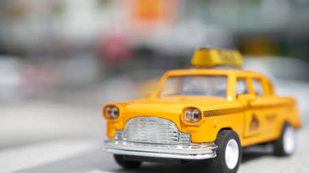Yellow vacant mini taxi cab close up, Harmon corner, Las Vegas, USA. Small retro car model on defocused background. Little iconic auto toy as symbol of transport in soft focus. Blurred shopping mall.