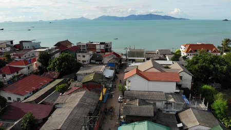 Fisherman village on seashore. Aerial view of typical touristic place on Ko Samui island with souvenir shops and walking street on sunny day. Architecture in asia, local settlement drone view.