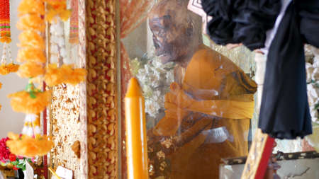 KOH SAMUI ISLAND, THAILAND - 17 JULY 2019: Wat Khiri Wongkaram Buddhist Temple. The mummified body of monk and gold leaf. Exotic tradition of storing the relics of saints who died during meditation Editorial