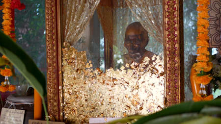 KOH SAMUI ISLAND, THAILAND - 17 JULY 2019: Wat Khiri Wongkaram Buddhist Temple. The mummified body of monk and gold leaf. Exotic tradition of storing the relics of saints who died during meditation