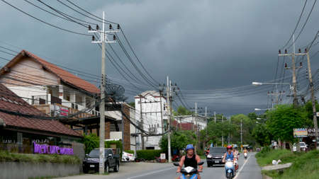 KOH SAMUI ISLAND, THAILAND - 11 JULY 2019 Busy transport populated city street in cloudy day. Typical street full of motorcycles and cars. Thick blue clouds before storm during wet season Editorial