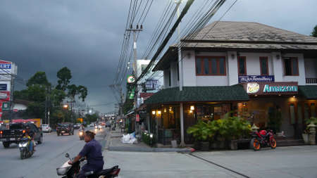 KOH SAMUI ISLAND, THAILAND - 21 JUNE 2019 Busy transport populated city street in cloudy day. Typical street full of motorcycles and cars. Thick blue clouds before storm during wet season