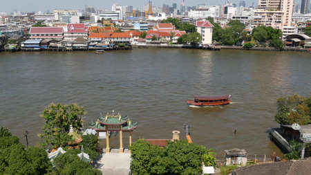 Oriental boat floating on river in Krungthep city. Modern transport vessel floating on calm Chao Praya river on sunny day in Bangkok near chinatown. Panorama.