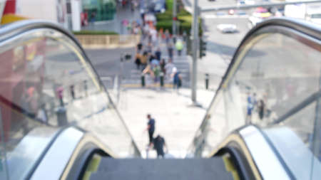 Perspective view thru escalator, defocused unrecognizable group of people on road intersection crosswalk on Strip of Las Vegas, USA. Anonymous blurred pedestrians on walkway in crowded urban downtown. Banque d'images