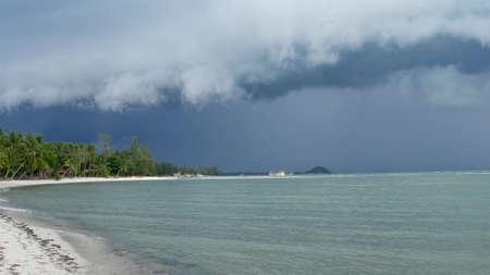 Waving blue sea, sandy shore of Samui Island during wet rain season, Thailand. Hurricane and storm warning on exotic tropical ocean beach. Fast wind and ominous clouds. Danger typhoon thunderstorm. Standard-Bild