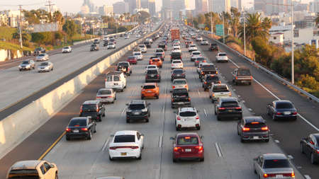 SAN DIEGO, CALIFORNIA USA - 15 JAN 2020: Busy intercity freeway, traffic jam on highway during rush hour. Urban skyline and highrise skyscrapers. Transportation concept and transport in metropolis. Editoriali