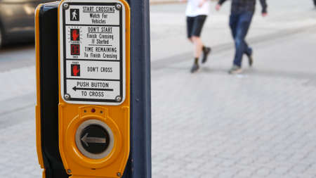 Traffic light button on pedestrian crosswalk, people have to push and wait. Traffic rules and regulations for public safety in USA. Zebra street crossing on road intesection in San Diego, California. 写真素材