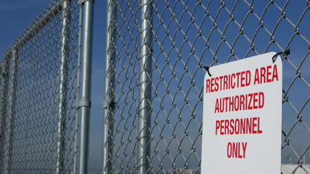 Restricted area, authorized personnel only sign in USA. Red letters, keep off warning on metal fence, United States border symbol. No trespassing notice means violators will be prosecuted by US law.