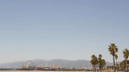 California beach aesthetic, classic ferris wheel, amusement park on pier, Santa Monica pacific ocean resort. Summertime iconic view, palm trees and sky, symbol of Los Angeles with copy space, CA USA.