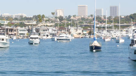 Newport beach harbor, weekend marina resort with yachts and sailboats, Pacific Coast, California, USA. Waterfront luxury suburb real estate in Orange County. Expensive beachfront holiday destination.