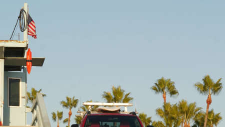 Iconic retro wooden lifeguard watch tower, baywatch red car. Life buoy, american state flag and palm trees against blue sky. Summertime California aesthetic, Santa Monica beach, Los Angeles, CA USA.