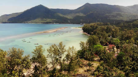 Aerial drone view island Koh Phangan Thailand. Exotic coast panoramic landscape, Chaloklum Malibu fisherman beach, summer day. Sandy path, corals. Vivid seascape, mountain coconut palms from above
