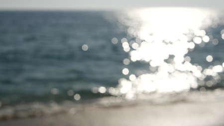 California summertime beach aesthetic, blurred defocused water wave. Shiny sun track and sunlight. Santa Monica pacific ocean resort. Dreamlike tranquil nebulous background. Unclear quiet idyllic sea.