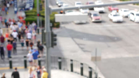 Defocused crowd of people, road intersection crosswalk on The Strip of Las Vegas, USA. Anonymous blurred pedestrians on walkway in crowded urban downtown. Unrecognizable american citizens in sin city.
