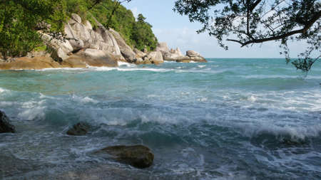 Green cliff near beautiful sea. Majestic blue sea rippling near rough green cliff of Ko Phangan on sunny day in Thailand. Exotic Tropical Paradise Beach