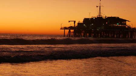 California summertime beach aesthetic, golden sunset. Vivid sky over pacific ocean waves. Santa Monica popular resort, Los Angeles CA USA. Famous pier against atmospheric moody evening sundown in LA.