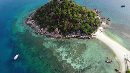 Calm colorful azure turquoise sea near tiny tropical volcanic island Koh Tao, unique small paradise Nang Yuan. Drone view of peaceful water near stony shore and green jungle on sunny day in Thailand