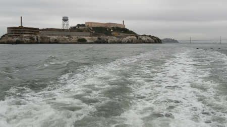Alcatraz island in San Francisco Bay, California USA. Federal prison for gangsters on rock, foggy weather. Historic jail, cliff in misty cloudy harbor. Gaol for punishment and imprisonment for crime.