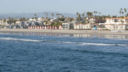 Oceanside, California USA - 11 Feb 2020: Local people walking strolling, pacific ocean coast, beach from pier. Sea water waves tide, shore sand. Beachfront vacations resort. Waterfront promenade.
