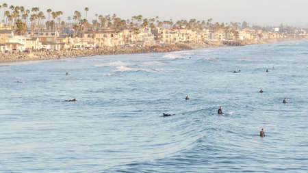 Oceanside, California USA - 16 Feb 2020: People surfing, surfers swimming in water and waiting sea wave, standing on surfboard. Aquatic sport hobby, healthy lifestyle. Pacific ocean tropical resort.