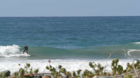 Encinitas, California USA - 23 Feb 2020: Surfers in ocean, pacific coast big blue sea water waves. People surfing, sport with surfboards. Healthy lifestyle, watersport hobby. Person and surf or tide.