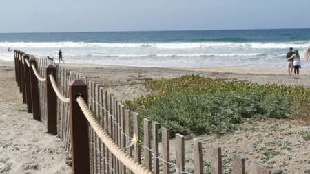 Encinitas, California USA - 23 Feb 2020: Pacific coast, people walking on ocean beach by sea water waves. Coastal access with picket fence on sandy shore near San Diego and Los Angeles. Couple and dog Editorial