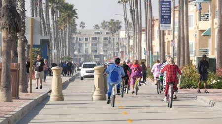 Oceanside, California USA - 8 Feb 2020: People walking on waterfront promenade, beachfront boardwalk near pier. Vacations ocean beach resort near Los Angeles. People in pajama riding bikes or bicycles Standard-Bild - 158644870