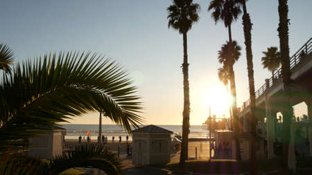 Oceanside, California USA - 27 Dec. 2019: Wooden pier and people walking. Tourists strolling in waterfront resort, summertime vacations near Los Angeles. Sunset ocean beach, tropical sunny orange sky.
