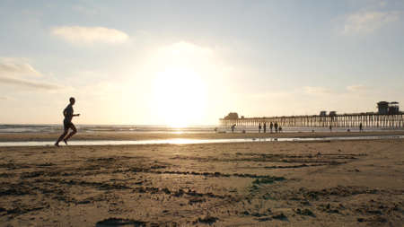 Oceanside, California USA - 8 Feb 2020: People walking on ocean beach, waterfront vacations resort. Contrast silhouette, man running, sand near sea waves. Young guy training in sunset light near pier.