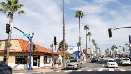Oceanside, California USA - 27 Jan 2020: Palm trees on typical american street, pacific coast tropical resort. Traffic light and auto transport on road intersection, cars on crossroad in summer city.